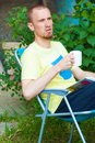 Man at backyard drinking coffee and reading book Royalty Free Stock Photo