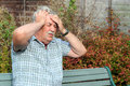 Man with a bad headache senior in pain he is holding his head two hands Royalty Free Stock Image