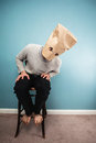 Man with bag over head on chair Royalty Free Stock Photos