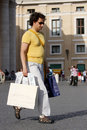 Man with bags purchases many of made concept of gender equality sunglasses and sandals yellow t shirt and shoulder bag location Royalty Free Stock Images