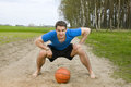 Man with ball frontal wide angle shooting of a young in a blue t shirt short black shorts and barefoot in low posture forward bent Stock Photography