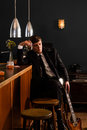 Man at a bar young in suit sits with his guitar and drinks alcohol Royalty Free Stock Image