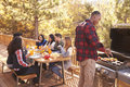 Man barbecues for friends at a table, on a deck in a forest Royalty Free Stock Photo