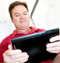 Man in Bathroom with Tablet PC Stock Photography