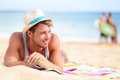 Man on beach lying in sand looking to side smiling happy wearing hipster summer hat young male model enjoying summer travel Royalty Free Stock Images