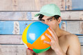Man at the beach portrait young handsome in front of wooden blue vintage background with ball and cap Stock Image