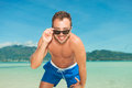 Man on the beach posing in briefs while fixing sunglasses Royalty Free Stock Photo