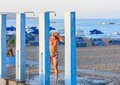 Man on the beach under the shower. Rhodes Island Royalty Free Stock Photo
