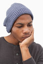 Man in beanie hat thinking with head on hand white background Royalty Free Stock Images
