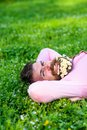 Man with beard on happy face enjoy nature. Unite with nature concept. Bearded man with daisy flowers in beard lay on Royalty Free Stock Photo