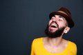 Man with beard and hat laughing close up portrait of a handsome young on gray background Stock Images