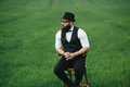 Man with a beard sitting on chair on the field Royalty Free Stock Image