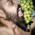 Man with beard who eats voraciously grapes Royalty Free Stock Photo