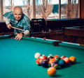 Man begins to play a game of billiards and breaks pyramid of bal Royalty Free Stock Photo