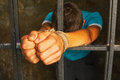 Man behind the bars with hands tied up with rope Stock Images