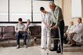 Man being helped by nurse to walk zimmer frame senior men female the with people sitting in hospital lobby Royalty Free Stock Photo