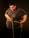 Man belly fat with tape measure weight loss around body . Royalty Free Stock Photo