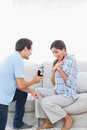 Man on bended knee offering an engagement ring to his girlfriend the couch Royalty Free Stock Photo