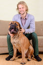 Man with big dog young at home playing a bullmastiff positively laugh Royalty Free Stock Photo