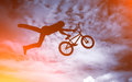 Man with a bike silhouette of doing an jump bmx against sunshine sky Royalty Free Stock Photography