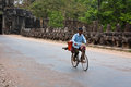 Man bikes past ruins at Angkor Wat Royalty Free Stock Photos