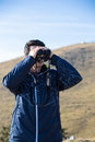 Man with binoculars image showing a young using his in the wild Stock Photos