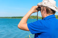 Man with binoculars looks for something on the lake Stock Images