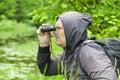 Man with binoculars watching birds at the lake Stock Photo