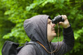 Man with binoculars watching birds in the park summer Stock Photo