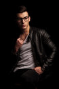 Man in black leather jacket wearing glasses pulling his shirt Royalty Free Stock Photo