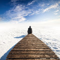 Man in black sit on old wooden pier winter coast of frozen baltic sea Royalty Free Stock Images