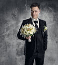 Man in black suit with flowers bouquet wedding groom fashion gray background Stock Photo