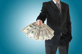 Man in  black suit offers money isolated on blue background Royalty Free Stock Photo