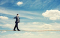 Man with the blindfold walking on rope over blue sky Royalty Free Stock Photography