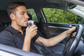 Man blowing into breathalyzer in car Stock Image