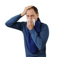 Man blowing his nose and holding his head Royalty Free Stock Photography