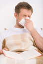 Man blowing his nose while lying sick in bed and reading book Stock Photo