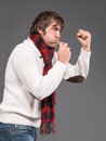 Man blowing a whistle and making a fist on gray background Royalty Free Stock Photography