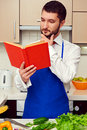 Man in blue apron reading cookbook Royalty Free Stock Photo