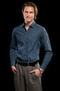 Man in blue shirt and grey slacks studio shot over black Royalty Free Stock Photos