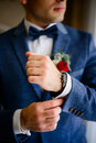 Man in blue suit adjusts white sleeve over watch Royalty Free Stock Photo