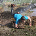 Man in blue tshirt makes a spectacular overturn in the mud stockholm may t shirt trying to avoid hanging electrified cabels during Royalty Free Stock Photography