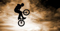Man with a bmx bike silhouette of doing an jump Stock Images