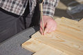 Man is bolting screwed into a wooden board in plaid shirt Stock Photos