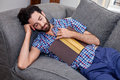 Man book sofa couch sleeping on while reading at home living room lounge Royalty Free Stock Photos