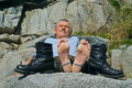 Man and boots is lying on stones with on foreground Royalty Free Stock Images