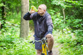 Man with bottle of water on bicycle in forest Royalty Free Stock Photo