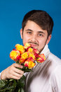 Man with bouquet of red roses on blue background Stock Photo