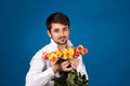 Man with bouquet of red roses on blue background Stock Photography