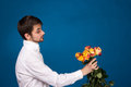 Man with bouquet of red roses on blue background Stock Photos